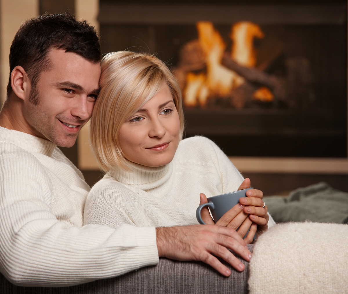 Young love couple hugging on sofa in front of fireplace at home, looking away, smiling.